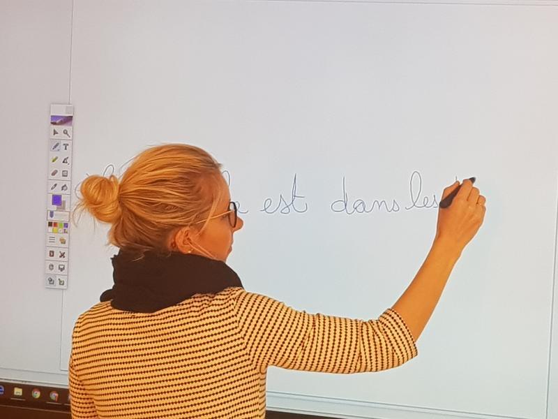 Une enseignante de Français à l'école de Notre Dame des missions utilise le logiciel interactif d'annotation pour écrire
